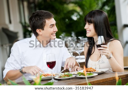 An attractive young couple shares a salad at an outdoor restaurant - stock photo