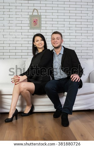 An attractive young couple sitting on the couch. Stylish couple in love on a white couch. The high sharpness and excellent quality. - stock photo