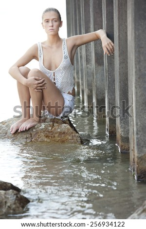 An attractive young female model wearing white shorts and a white top posing outdoors standing in the water. - stock photo