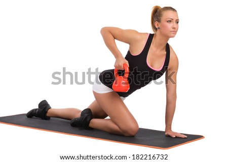 An attractive young female on exercise mat. Fitness instructor with Kettlebell show how to exercises triceps. Full length studio shot isolated on white. - stock photo