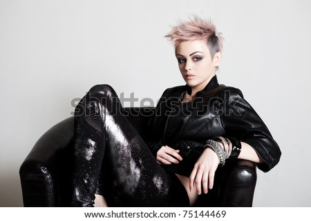 An attractive young female with a serious expression is sitting in a chair and wearing punk attire. Horizontal shot. - stock photo