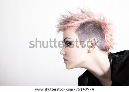 An attractive young female with a serious expression is wearing a punk hairstyle with pink hair. Horizontal shot. - stock photo