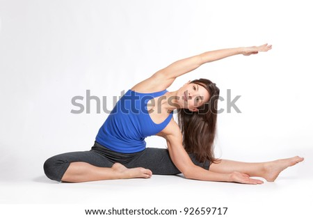 An attractive young, fir, slim, woman smiles while doing yoga