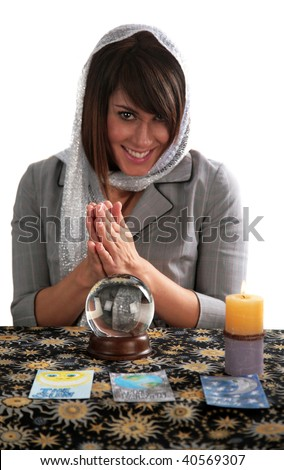 an attractive young fortune teller, looks into the future with her crystal ball, isolated on white,  with room for your text - stock photo
