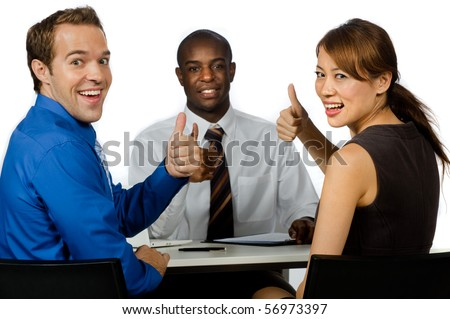 An attractive young group of business professionals giving the thumbs up in their office against white background - stock photo