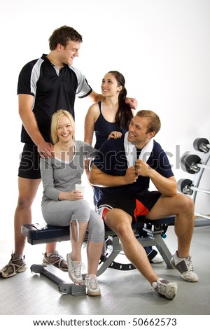 An attractive young group of friends relaxing in the gym after a workout - stock photo