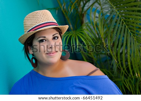 An attractive young Hispanic woman smiling with her hat and outdoors by some tropical foliage. - stock photo