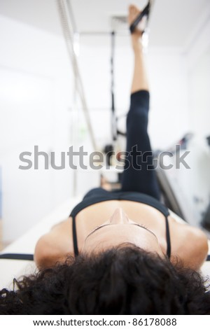 An attractive young lady performing a Pilates exercise with resistance from equipment. - stock photo