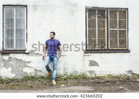An Attractive young man is standing on the street wall - stock photo