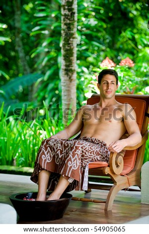An attractive young man relaxing at a spa outdoors - stock photo