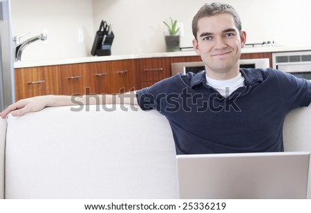 An attractive young man uses a laptop at home. - stock photo