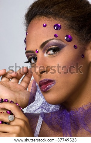 An attractive young model with glamorous makeup and gemstones. - stock photo