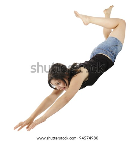 An attractive young teen mid-air, falling (or flying) with hands and head first.  On a white background. - stock photo