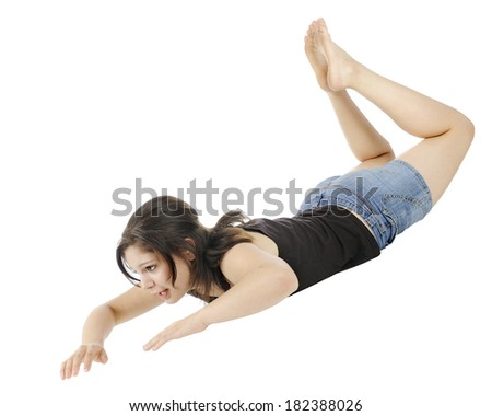 An attractive young teen moving down through the air hands and head first.  On a white background. - stock photo