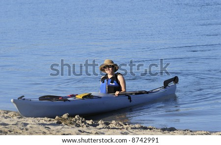 An attractive young woman a little flushed with excitement came to a shore after a kayak ride in calm waters of Mission Bay, San Diego, California. Ample copyspace on top. - stock photo