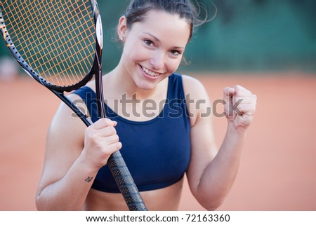 An attractive young woman celebrating after winning a tennis match - stock photo