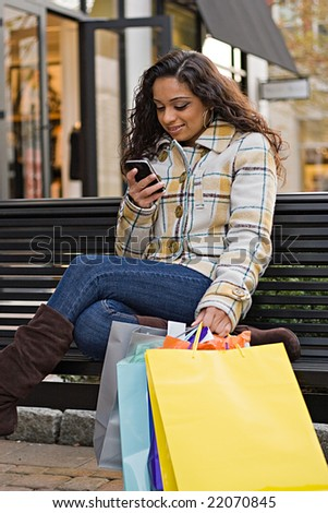 An attractive young woman checking her cell phone while out shopping in the city. - stock photo