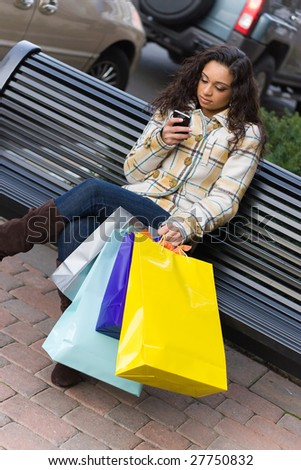 An attractive young woman checking her cell phone while out shopping in the city.  She might be texting or surfing the internet. - stock photo