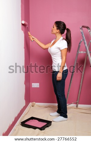 An attractive young woman decorating the wall of her new home - stock photo