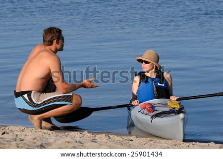 An attractive young woman discusses sea kayaking with a man on a beach. Mission Bay, San Diego, California - stock photo