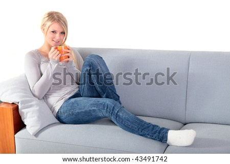 An attractive young woman enjoys a cup of coffee while sitting on a couch. - stock photo
