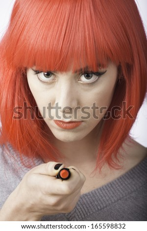 An attractive young woman gestures with a red lipstick. She is wearing a matching red wig.