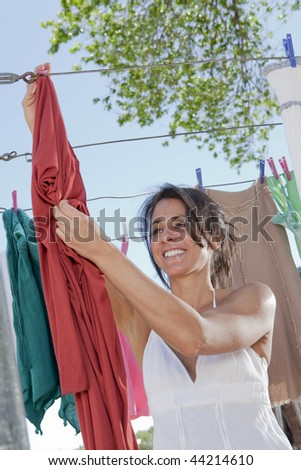 An attractive young woman hanging laundry. - stock photo