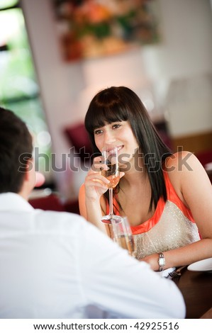 An attractive young woman holding a glass of white wine and smiling at her partner at a restaurant - stock photo