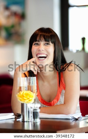 An attractive young woman holding a glass of white wine in a restaurant
