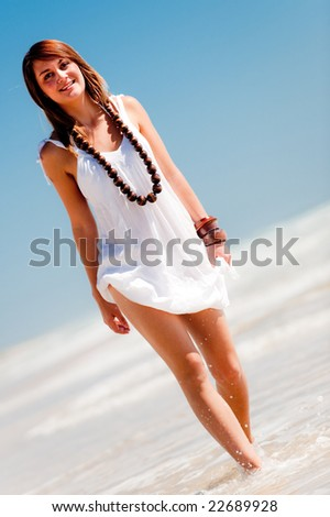 An attractive young woman on a deserted beach - stock photo