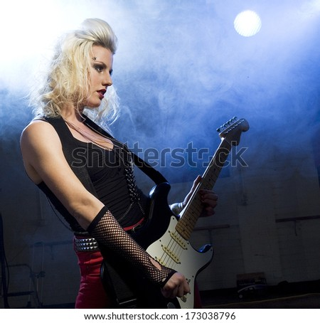 An attractive young woman plays guitar on a stage with lights shining through smoke behind her./Female guitarist - stock photo
