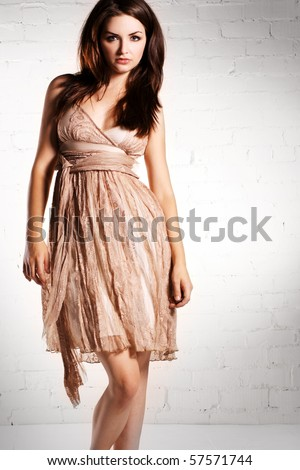 An attractive young woman posing in a lovely dress. - stock photo