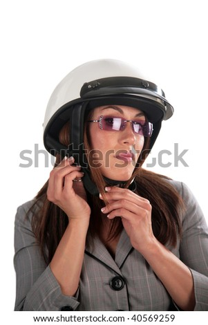 An attractive young woman puts on her motorcycle helmet, isolated on white