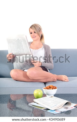 An attractive young woman reading the newspaper while sitting on the couch.