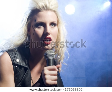 An attractive young woman sings on a stage with lights shining through smoke behind her./Female vocalist