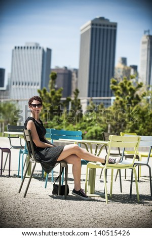 an attractive young woman sitting outside in a big city - stock photo