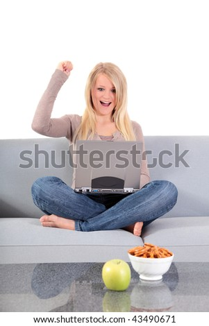 An attractive young woman using her notebook computer while sitting on a couch. - stock photo