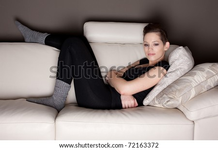 An attractive young woman watching TV, lying on the couch - stock photo