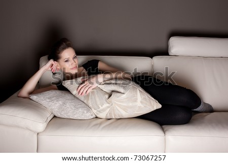 An attractive young woman watching TV, lying on the couch comfortably - stock photo