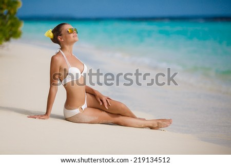 An attractive young woman wearing a black bikini sits on a beach with her elbow on her knee and her hand to her head. Surf can be seen in the background. Horizontal shot. - stock photo
