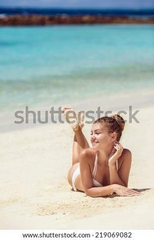 An attractive young woman wearing a white bikini laying on a beach with her elbow on the sand. Ocean can be seen in the background. Vertical shot. - stock photo