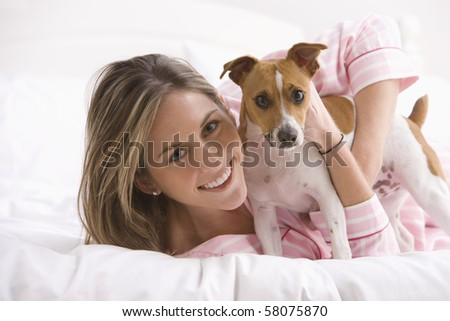 An attractive young woman wearing pink pajamas is holding a dog while laying on a bed. Horizontal shot.