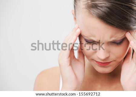 An attractive young woman with her eyes closed is rubbing at her temples to relieve a headache - stock photo