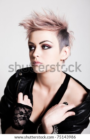 An attractive young woman with pink hair wearing a leather jacket and lace glove. Vertical shot. - stock photo