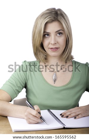 An attractive young woman writes in a spiral bound book. She is dressed in green.