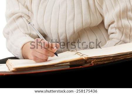 An attractive young woman writing on a notebook. - stock photo