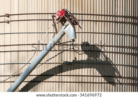 An auger attached to a concrete silo on a farm creates a wonderful shadow of its mechanical structure. - stock photo