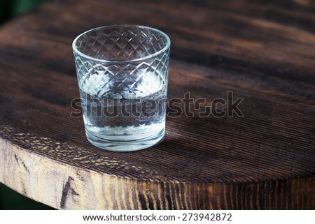 An authentic glass of drinking water on the old wooden table. Full-time atmospheric lighting, fashionable trendy spot soft focus. Preparation for creative design. - stock photo