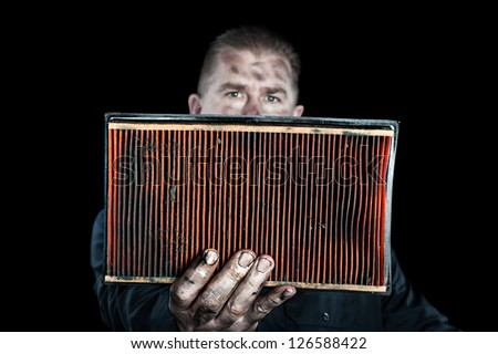 An auto mechanic holds up a filthy, grungy air filter removed from a car during normal maintenance. - stock photo