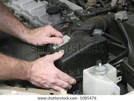 An auto mechanic removing the cover from a car air filter. - stock photo